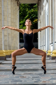 Beautiful slender sports woman dancer in a black suit and pointe dancing