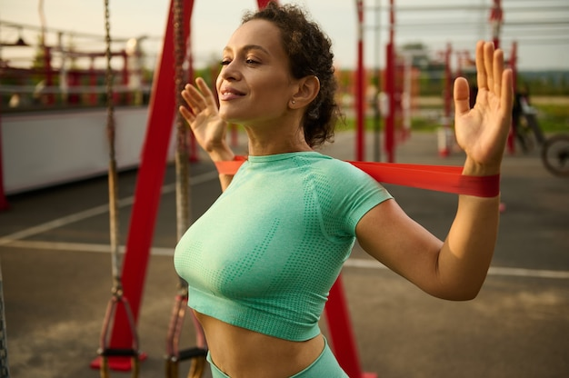 Beautiful slender sporty female athlete doing training with rubber resistance band on a sportsground. attractive african american, mixed race fit woman stretches her back and shoulders muscles.