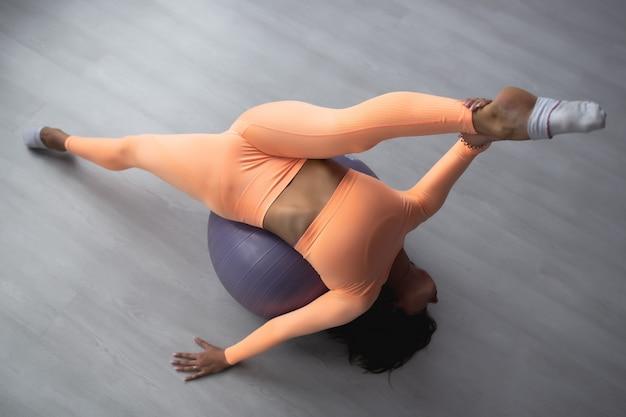 Красивая стройная женщина в спортивном комбинезоне занимается растяжкой