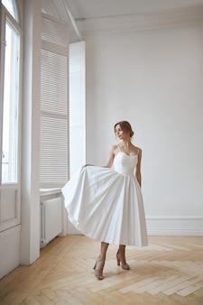 Красивая стройная женщина в белом свадебном платье, новая коллекция платьев для невесты. шум, не в фокусе