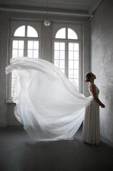 하얀 웨딩 드레스의 아름다운 날씬한 여자, 신부를위한 드레스의 새로운 컬렉션. 노이즈, 초점이 맞지 않음