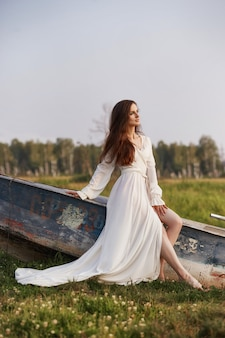 Beautiful slender woman in a long white dress walks in the morning near the lake. brown-haired girl with long hair walks on the grass in the village, natural cosmetics and makeup