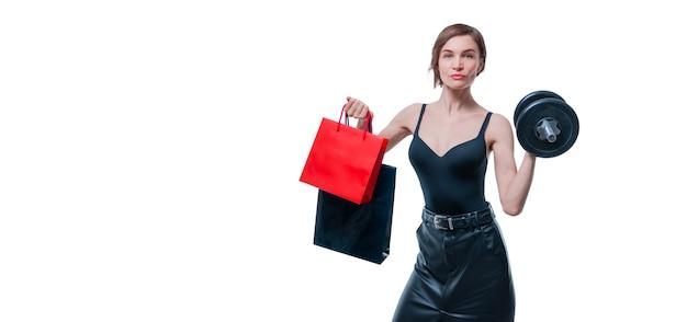 Красивая стройная женщина позирует в студии с гантелями и подарочными пакетами