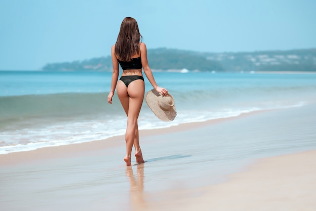 A beautiful and slender woman walks along the sea coast with a straw hat in her hands. back view. copy space