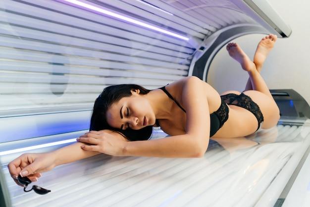 Красивая стройная молодая девушка лежит в горизонтальном солярии, загорая под ультрафиолетовыми лучами