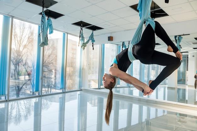 Девушка красивого стройного тела практикует летать йогу в тренажерном зале. fly йога спорт