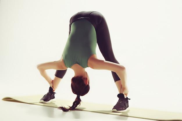 ジムでいくつかのストレッチ体操をしている美しいスリムなブルネット