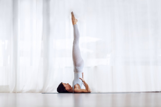 Beautiful slim brunette in supported shoulder stand yoga position. yoga studio interior.