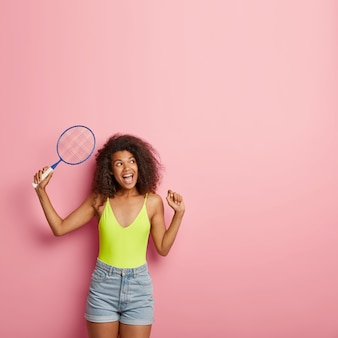 美しいスリムなのんきな暗い肌の女性はバドミントンやテニスをし、ラケットを保持します