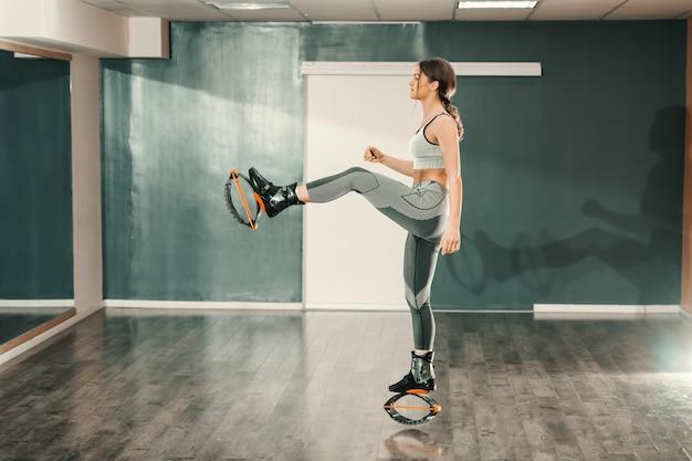 Kangoo를 착용하는 동안 한쪽 다리에 서있는 운동복에 아름 다운 슬림 백인 여자 신발 점프.