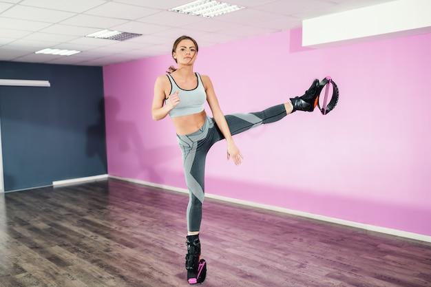 カングーを着用しながら片足でスポーツウェア立って美しいスリムな白人女性は靴をジャンプします。