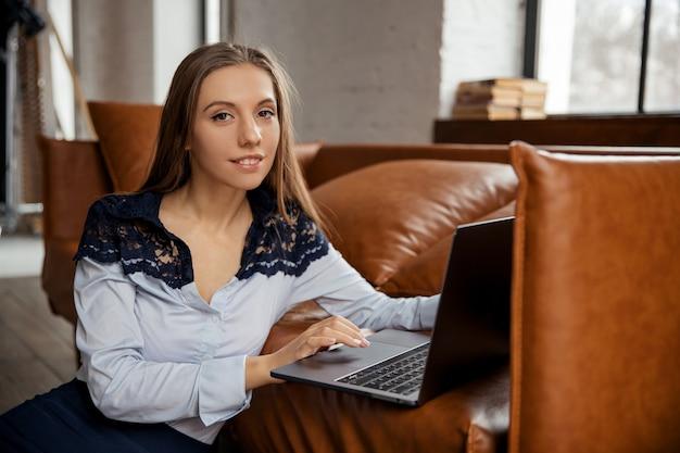 Красивая стройная элегантная молодая бизнес-леди, работающая удаленно из дома с помощью ноутбука. фото высокого качества
