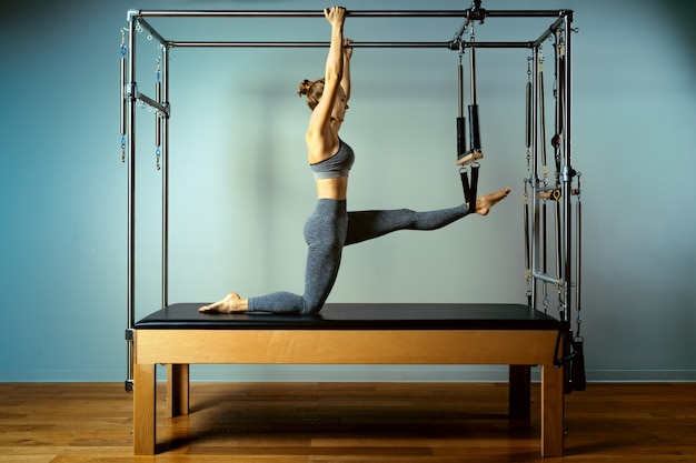 Beautiful slim fitness trainer on reformer gray background, low key, art light.