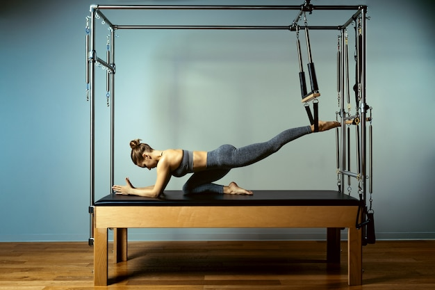 Beautiful slim fitness trainer on reformer gray background.