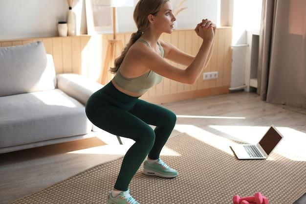 Красивая тонкая женщина фитнеса приседает. спорт, здоровый образ жизни. девушка занимается спортом дома.