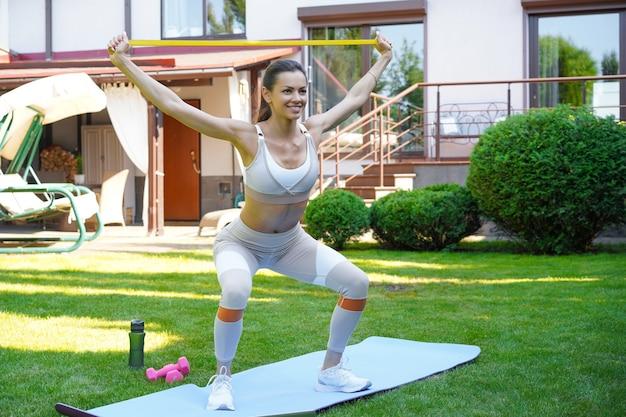 Красивая тонкая женщина фитнеса приседает. спорт, здоровый образ жизни. девушка занимается спортом на открытом воздухе дома.