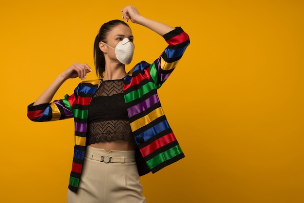 Beautiful slim girl fashion model posing in a protective respirator on a yellow background. lgbt community rainbow color jacket