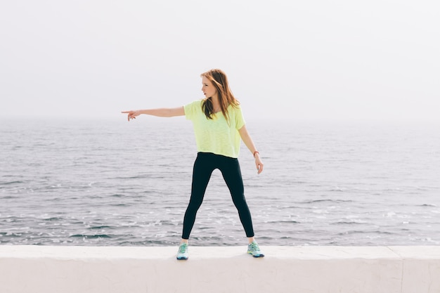 Beautiful slim girl in green sportswear shows the direction of the hand on the background of the sea