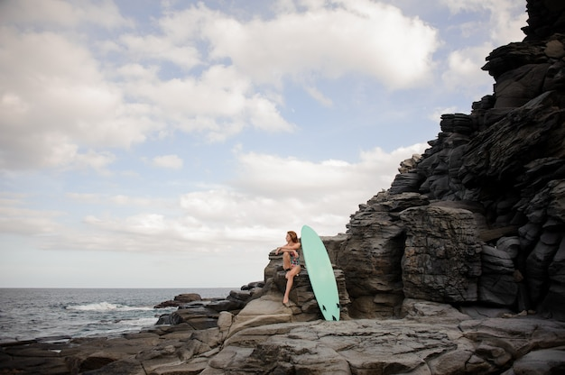 Beautiful slim girl in the multi colored swimsuit sitting near the surfboard on the rock over the atlantic ocean and clear sky