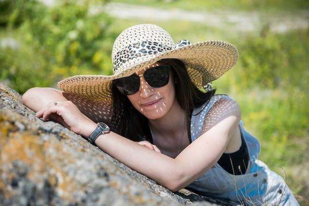 夏に自然の中でポーズをとる美しいスリムな女の子。