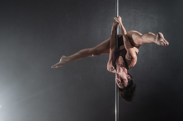 Beautiful slim girl with pylon female pole dancer dancing on a black background