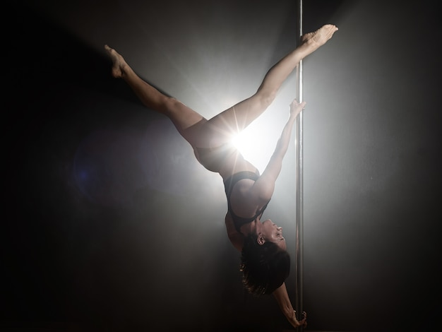 Beautiful slim girl with pylon. female pole dancer dancing