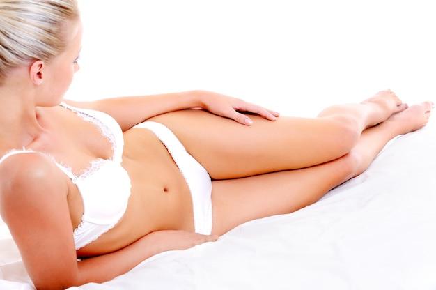 흰색 침대에 누워 아름다운 슬림 다리와 완벽한 여자 몸