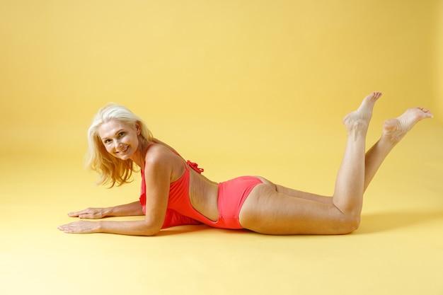 ポーズスタジオの床に横たわっている間カメラに微笑んで赤い水着の美しいスリムな成熟した女性