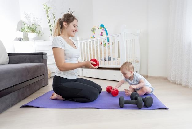 自宅のフィットネスマットに座ってダンベルで運動している彼女の赤ん坊の息子と美しいスリムな母親