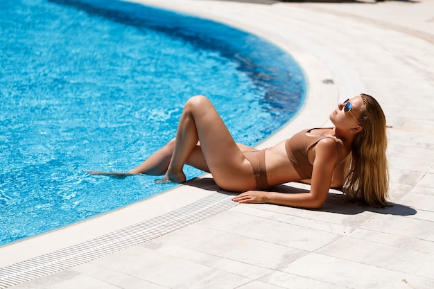 Beautiful slim sexy young woman with long blond hair in a beige swimsuit resting near the pool with blue water
