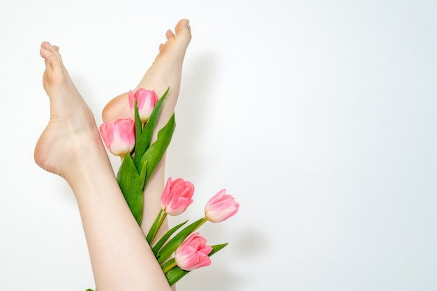 Красивые стройные гладкие женские ноги с цветами тюльпанов на белом фоне