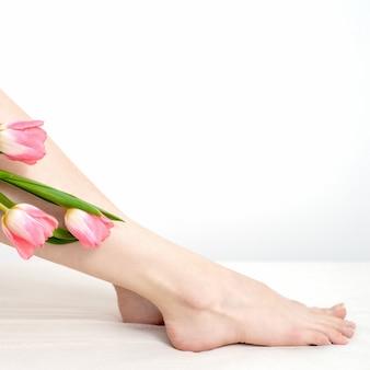 흰색 바탕에 튤립 꽃과 아름 다운 슬림 부드러운 여자의 다리