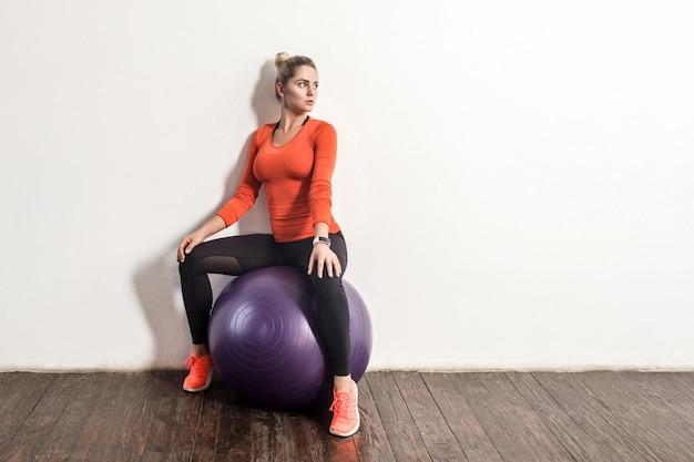 꽉 끼는 운동복을 입은 아름다운 날씬한 스포티 여성은 큰 피트니스 고무 공에 앉아 휴식을 취하고 체육관 집에서 훈련을 한 후 쉬고 있습니다. 건강 관리, 스포츠 활동 및 운동. 실내 스튜디오 촬영