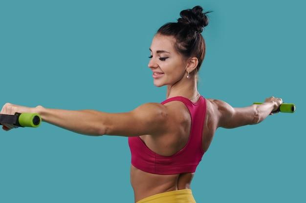 Красивая стройная спортивная женщина с вытянутыми руками держит гантели и позирует боком перед камерой