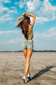上に手で美しいスリムな日焼けしたフィットネス女の子の背中。スタイリッシュなジーンズのショートパンツで屋外でポーズ。やわらかい光。
