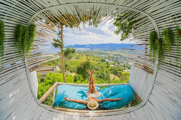 Beautiful slim tourist woman is lying down sunbathing, covered had with huge straw hat, near terrace in cafe outdoor with scenic view on mountains. time to relax.
