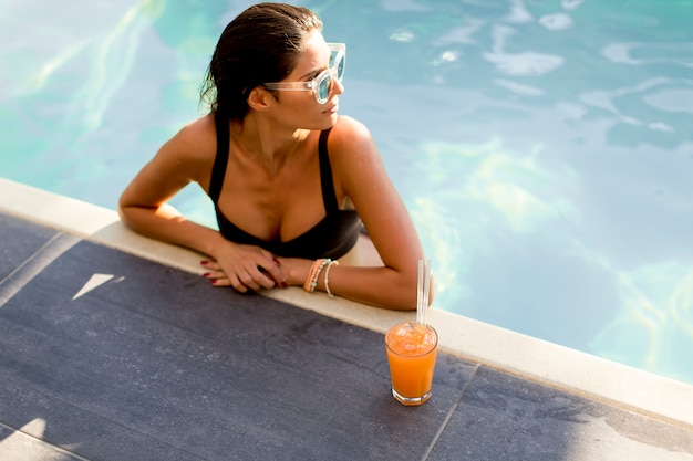 Beautiful slim woman in bikini and sunglasses relaxing and drink cocktail on poolside of a swimming pool