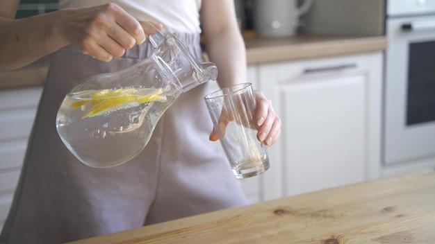 美しいスリムな女性はデトックスのためにレモン水を飲みます。若い女性がデカンターからレモン水を注ぎ、それを飲みます。健康的な食事と減量の概念。 4k uhd