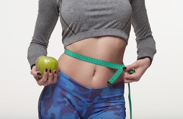 青リンゴと彼女の腰にいくつかの色測定テープを保持している美しいスリムな女性