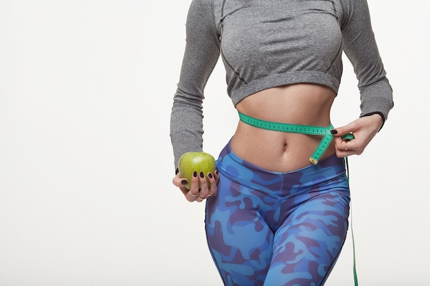 Beautiful slim woman holding green apple and with several color measuring tapes on her waist