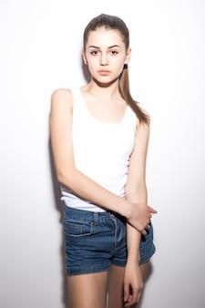 Красивая стройная женщина в футболке, на белом