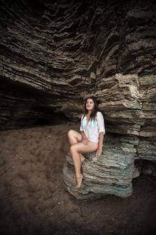 海の洞窟で大きな崖の上に座っている美しいスリムな女性