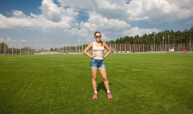 Beautiful slim woman standing on soccer field at sunny day