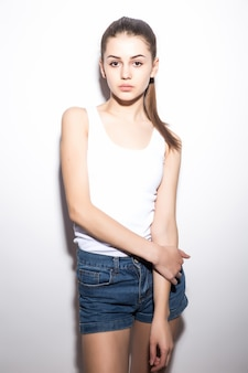 Beautiful slim woman in a t-shirt, on white