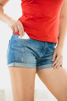 Beautiful slim woman taking condom out of jeans shorts