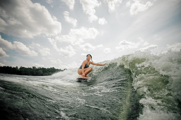 Beautiful slim woman wakesurfing on the board against the sky