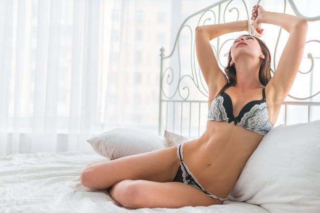 白いカーテンの背景の上にベッドに座っている黒と白のセクシーな下着の美しいスリムな若いブルネットの女性。性的なゲームの概念