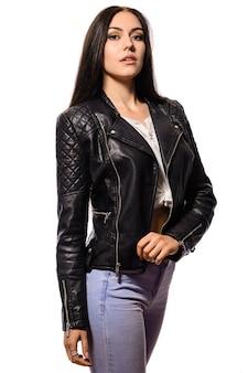 黒革黒革のジャケットに立っている長い黒髪の美しいスリムな若い女性