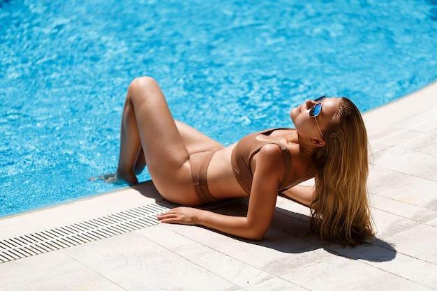 Beautiful slim young woman with long blond hair in a beige swimsuit resting near the pool with blue water