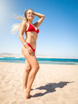 Beautiful slim young woman with long hair wearing sexy red bikini posing on the beach against sea waves and blue sky